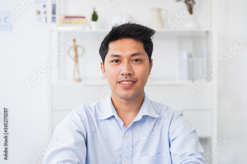 Fotografiet Screen of Asian businessman talking while video call or virtual meeting in offic