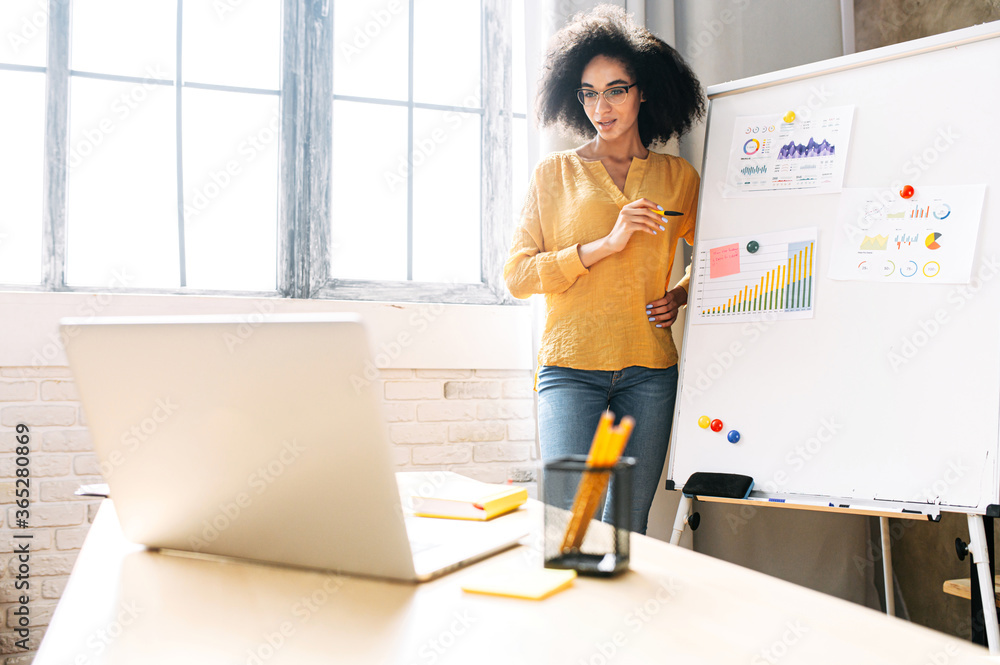 Fototapeta Dark skinned young woman is conducts online webinars, online classes, online presentation. African girl explains something on a flip-chart in a office classroom to virtual audience on a laptop