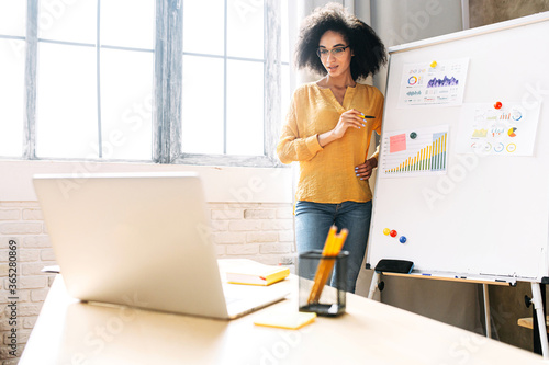 Obraz Dark skinned young woman is conducts online webinars, online classes, online presentation. African girl explains something on a flip-chart in a office classroom to virtual audience on a laptop - fototapety do salonu