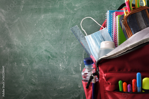 Backpack full of school supplies with mask and gel