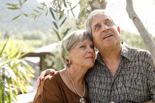 Coppia di anziani bianchi si abbracciano teneramente all'interno di un parco Wallpaper Mural