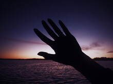 Close-up Of Silhouette Hand Against Sea During Sunset