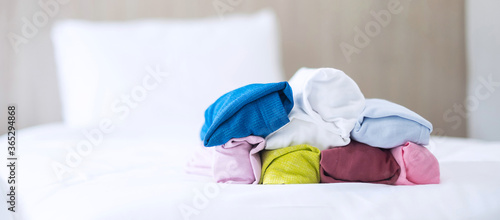 Obraz na plátně Stack of colorful T shirt on bed in luxury hotel or resort or home