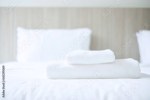 Vászonkép Stack of white towel and Bathrobe on bed in luxury hotel or resort