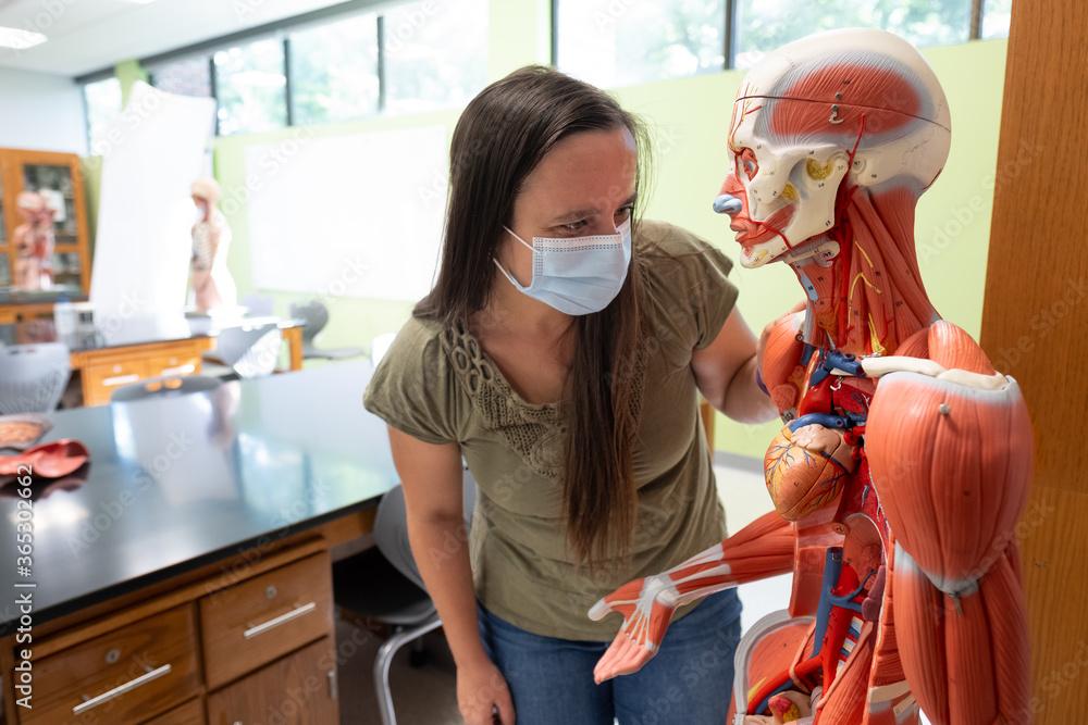 Fototapeta Female student wearing Covid 19 face mask in biology classroom