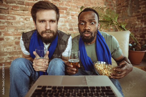 Excited football fans watching sport match at home, remote support of favourite team during coronavirus pandemic outbreak Canvas
