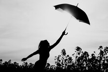 Unplugged Free Silhouette Woman Umbrella Up To Black White Sky. Nature Girl At Windy Rainy Day Has Adventure Wanderlust. Wonderful Scene Of Imagination Power And Departure To New Horizons In Youth
