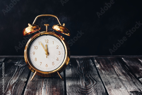 Obraz Gold alarm clock on a vintage wooden dark table. Rustic style. Selective focus, copy space. Time five minutes to twelve. - fototapety do salonu