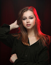 Girl In A Men's Black Shirt On A Dark Background With Red Highlighting Hair