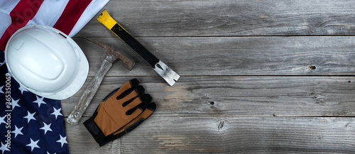 Waving US flag with construction tools on weathered wooden background for Labor Fotobehang