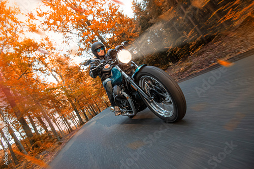 Motorcycle driver riding in autumn forest, blur motion effect Fototapeta