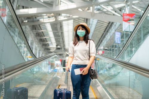 Asian traveler  woman with luggage wearing face mask looking outside terminal in airport standing on escalator go to gate for journey Canvas