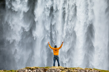 Man admirnig the beauty of iconic Skogafoss waterfall in Iceland, Europe.
