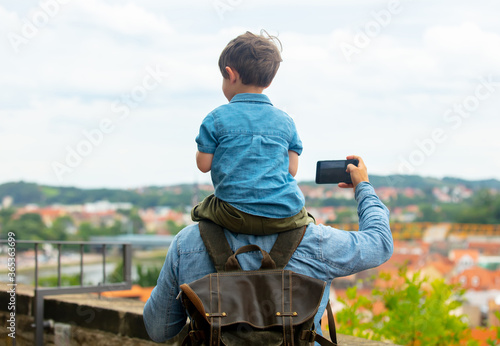 Obraz child sits on his father's shoulders while walking through the streets of the old city - fototapety do salonu