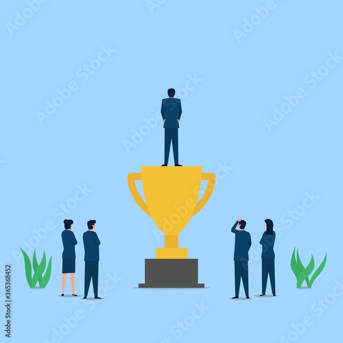 Photo Man stand above the trophy while other see metaphor of success and appreciation