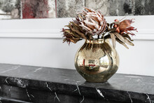 Minimalistic Composition Of Dried Artichoke Flowers In In A Round Glass Vase As Home Decoration. Decor In A Round Pot Reflects The Light Interior Of The Room