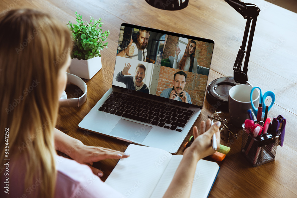 Fototapeta Remote meeting. Woman working from home during coronavirus or COVID-19 quarantine, remote office concept. Young boss, manager in front of laptop during online conference with colleagues and team.