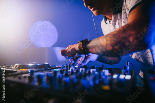 Fotografie, Obraz Techno male Caucasian DJ with headphones playing music on a mixer board in a blue background