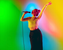 Bright Mood. Young Female Caucasian Inspired And Expressive Musician, Singer Performing On Multicolored Background In Neon. Concept Of Music, Hobby, Festival, Art. Joyful Artist, Colorful Portrait.