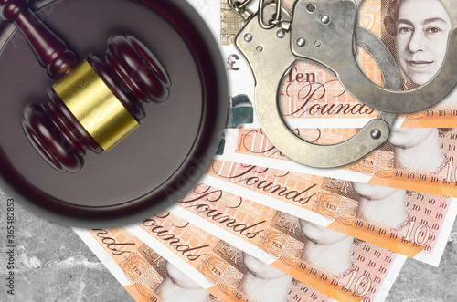 10 British pounds bills and judge hammer with police handcuffs on court desk Wallpaper Mural