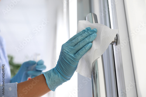 Fotografiet Woman cleaning door handle with wet wipe indoors, closeup
