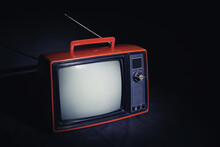 Retro Red Old TV With Antenna In Dark Room, Vintage Television On Black Floor.
