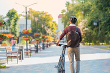 Male Commuter Wearing Bike Helmet Walking Away. Safe Cycling In City, Bicycle Commuting, Active Urban Lifestyle Image