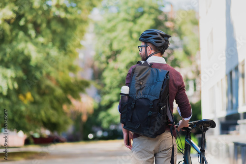 Male commuter or messenger with a bike in urban background Fotobehang
