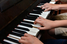 Brother And Sister Play The Piano With Four Hands. Children Learn The Art Of Music.