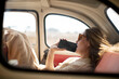 melancholic woman with mobile phone inside retro car