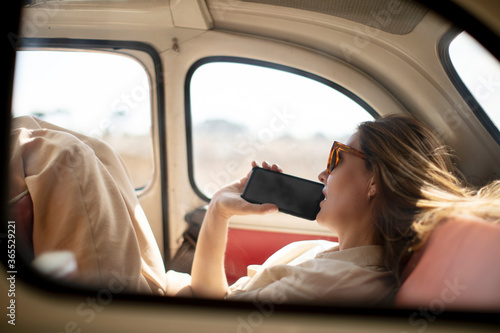 Fototapeta melancholic woman with mobile phone inside retro car