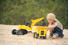 Child, Little Boy Have Fun With Toy Excavator And Dumper In The Sand. Carefree Childhood.
