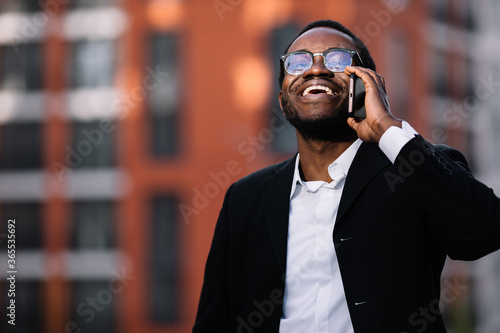 Photo Young stylish man talk on phone and smile