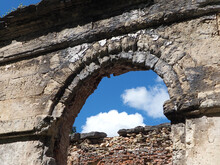 Arched Opening Of A Ruined Ancient Red Brick Building Against A Blue Cloudy Sky