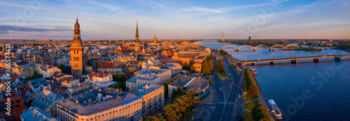 Flying over beautiful old town of Riga, Latvia at sunset with Domes cathedral and golden cock statue in the foreground Fotobehang