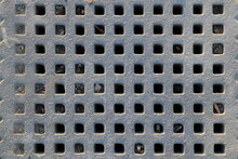 Close-up Of A Gray Stone Sildewalk Grate Exhibiting A Rough Texture And Squarish Holes In A Grid Pattern. Random Holes Are Partially Or Fully Filled With Dirt And Small Pieces Of Wood Or Rock. Subtle