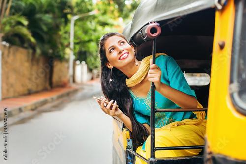 Fototapeta Pretty Indian woman in a auto rickshaw  with phone