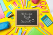 Text Welcome back to school and school supplies on yellow background