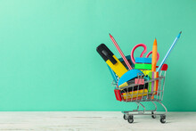 Shopping Trolley With School Supplies On Mint Background, Space For Text