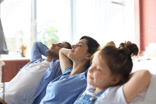 Obraz na plátne Relaxed young family resting and dreaming about new home on comfortable sofa together at home, happy young parents with little daughter relax enjoying nap relaxing or meditating