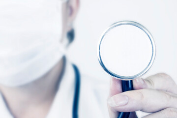 A stethoscope for examining a patient against the background of a doctor in a white medical mask. Healthcare concept