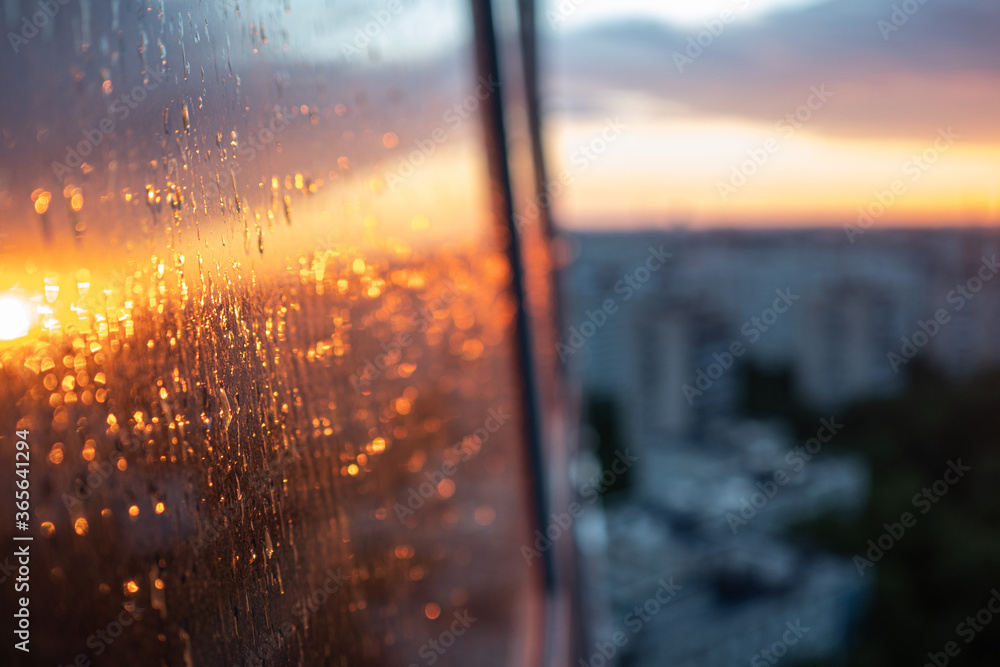 Fototapeta wet the window glass and the reflection of the sunset, the texture of the glass with rain drops.