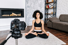 Young Sporty Slim Mixed-race Woman Yoga Coach Records Video Online Training Yoga. An African-American Girl Sits In Lotus Pose And Looks At Camera