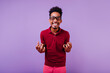 canvas print picture - Short-haired curly male model laughing to camera. Inspired african guy in glasses posing on purple background.