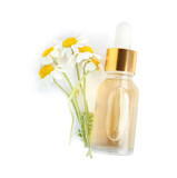 Fototapeta Kawa jest smaczna - Bottle of essential oil and chamomiles isolated on white, top view