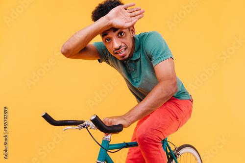 Valokuva Amazed black guy in casual t-shirt sitting on bicycle