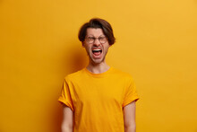 Emotional Guy Keeps Mouth Wide Opened, Screams From Disappointment, Shouts With Closed Eyes, Feels Troubled As Lost Huge Bet, Dressed In Bright Yellow T Shirt, Looses Temper, Has Life Problems