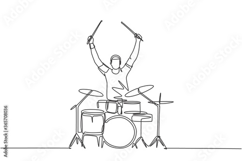 Fotografia One single line drawing of young happy male drummer raise drumstick up while play drum set on music concert stage
