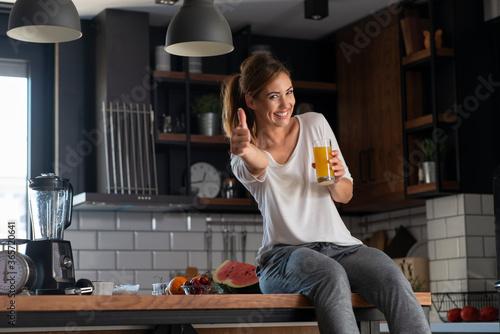 Obraz Portrait of a beautiful women holding glass with tasty juice indoors - fototapety do salonu