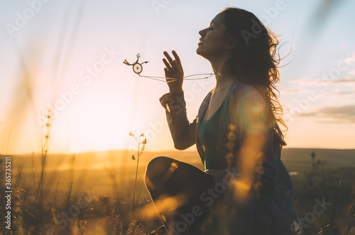 Fototapeta Portrait of a young woman at sunset with beautiful Balinese sacred geometry necklace in motion obraz